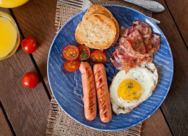 イングリッシュブレックファスト-木製のテーブルで素朴なスタイルのトースト、卵、ベーコン、野菜