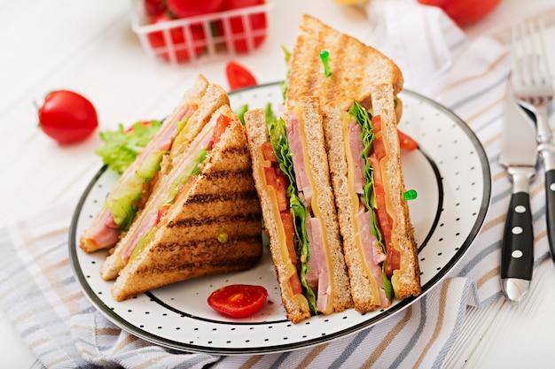 クラブサンドイッチ-ハム、チーズ、トマト、ハーブのパニーニ。