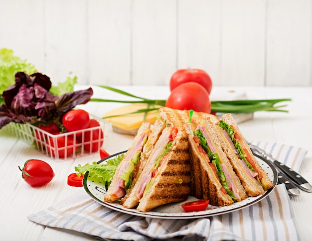 Клубный сэндвич - панини с ветчиной, сыром, помидорами и зеленью.