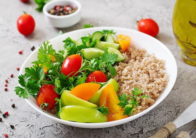 ダイエットメニュー。新鮮な野菜-トマト、キュウリ、ピーマン、お粥のボウルのヘルシーなベジタリアンサラダ。ビーガンフード。