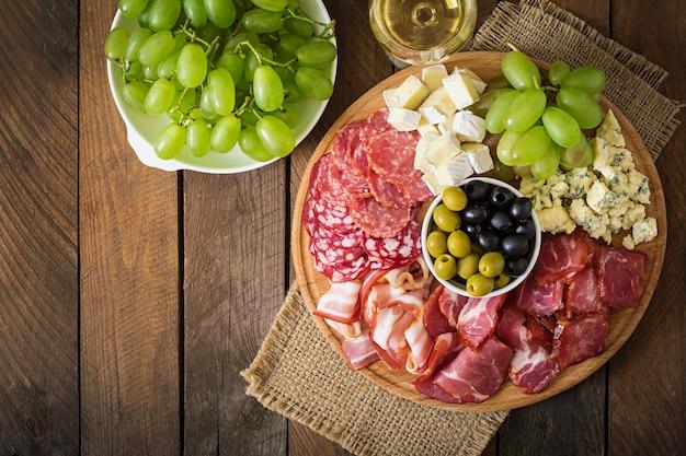 Антипасто блюдо с беконом, вяленым мясом, салями, сыром и виноградом на деревянном столе