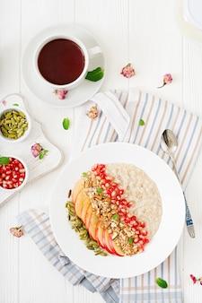 りんご、ザクロ、ナッツ入りのヘルシーなオートミールのお粥。健康的な朝食。フィットネス食品。適切な栄養。上面図。