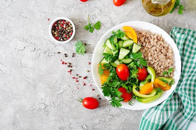ダイエットメニュー。新鮮な野菜-トマト、キュウリ、ピーマン、お粥のボウルのヘルシーなベジタリアンサラダ。ビーガンフード。フラット横たわっていた。上面図