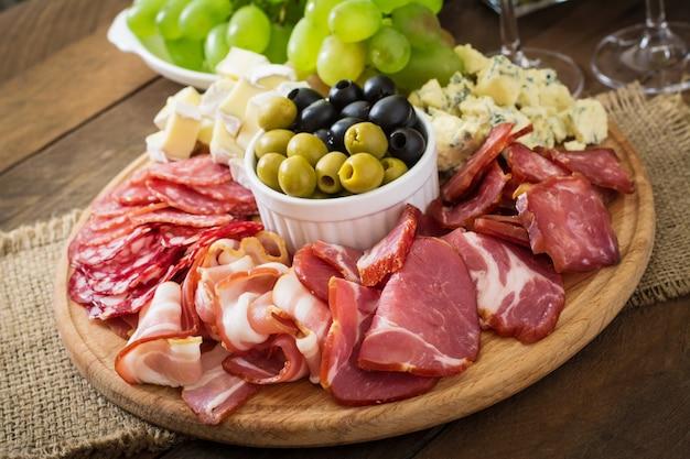 ベーコン、ジャーキー、サラミ、チーズ、木製のテーブルのブドウの盛り合わせ前菜