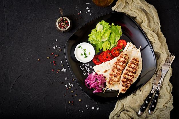 Фарш из люля кебаб на гриле, индейка (курица) со свежими овощами. вид сверху