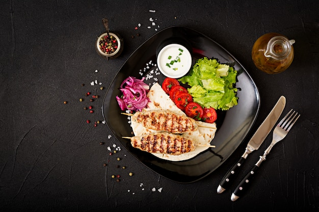 みじん切りのルラケバブ七面鳥のグリル(チキン)と新鮮な野菜。上面図