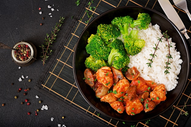Кусочки куриного филе с грибами, тушенные в томатном соусе с отварной брокколи и рисом. правильное питание. здоровый образ жизни. диетическое меню. вид сверху