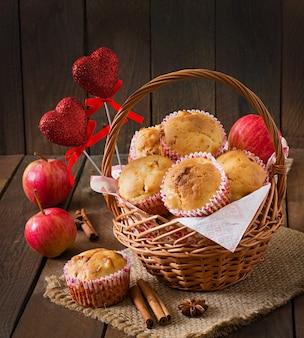 ナツメグと木製のテーブルの枝編み細工品バスケットのオールスパイスとフルーツのマフィン