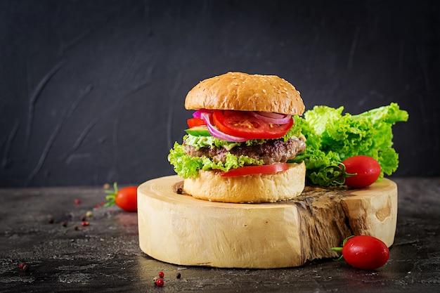 牛肉のハンバーガーと暗いテーブルで新鮮な野菜のハンバーガー。おいしい食べ物。