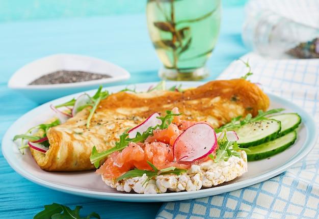 朝ごはん。大根、緑のルッコラと白い皿にサーモンのサンドイッチのオムレツ。フリッタータ-イタリアのオムレツ。