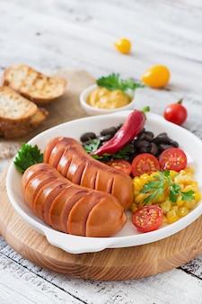 木製のテーブルのグリル鍋にソーセージ