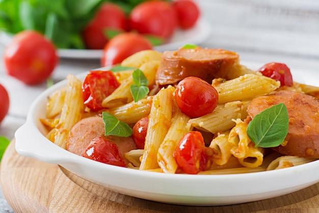 Паста пенне с томатным соусом с колбасой, помидорами, зеленым базиликом украшенная на сковороде на деревянном столе