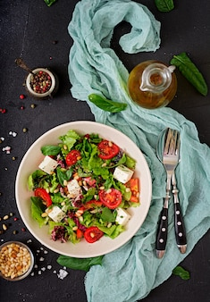 Диетический салат с помидорами, сыром фета, листьями салата, шпинатом и кедровыми орехами. вид сверху. квартира лежала.