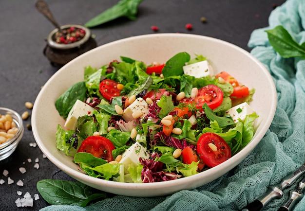 Диетический салат с помидорами, сыром фета, листьями салата, шпинатом и кедровыми орехами.