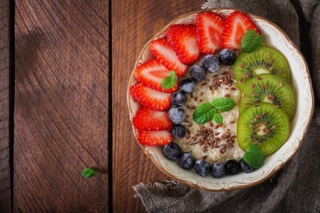 フルーツ、ベリー、亜麻の種子が入った、美味しくて健康的なオートミールのお粥。健康的な朝食。フィットネス食品。適切な栄養。フラット横たわっていた。上面図