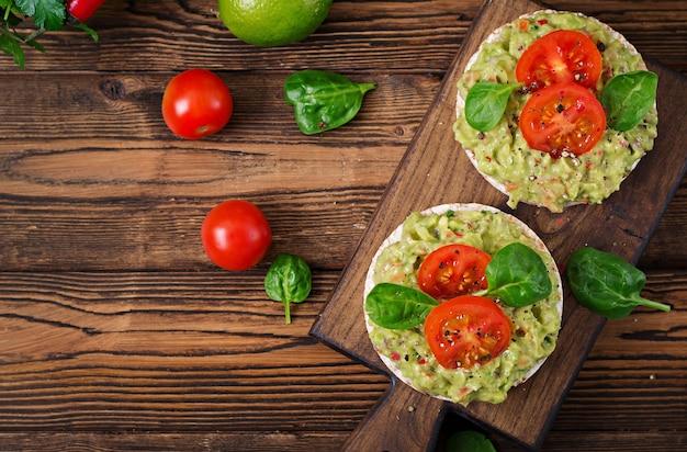 Здоровый завтрак. сэндвич хрустящий хлеб с гуакамолом и помидорами