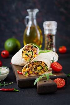 ブリトーは牛肉と野菜を黒の背景に包みます。ビーフブリトー、メキシコ料理。