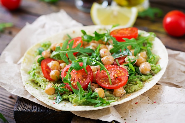 ビーガンタコス、ガーコカモール、ヒヨコマメ、トマト、アールーグラ。健康食品。便利な朝食