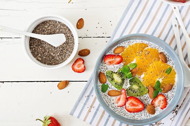 健康的なスーパーフード。ビーガンアーモンドミルクチア種子プリン、いちご、オレンジ