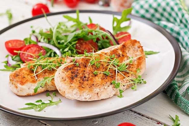 焼きチキンの切り身とトマト、赤玉ねぎとルッコラの新鮮野菜のサラダ。