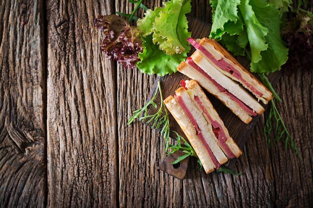 クラブサンドイッチ - 木製の背景にハムとチーズのパニーニ。ピクニックフード