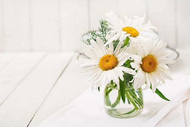 Букет из ромашек в вазе на деревянном белом столе