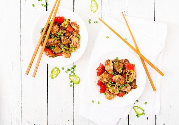 Домашняя курица кунг пао с перцем и овощами. китайская еда. жарить в раскаленном масле. вид сверху. плоская планировка