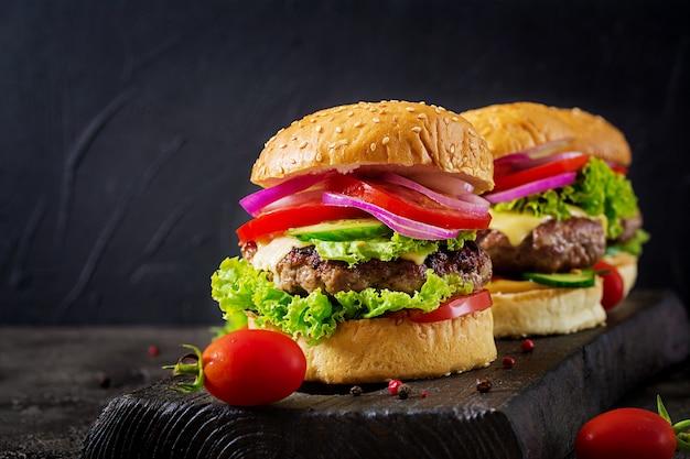 牛肉のハンバーガーと暗い背景に新鮮な野菜のハンバーガー。おいしい食べ物