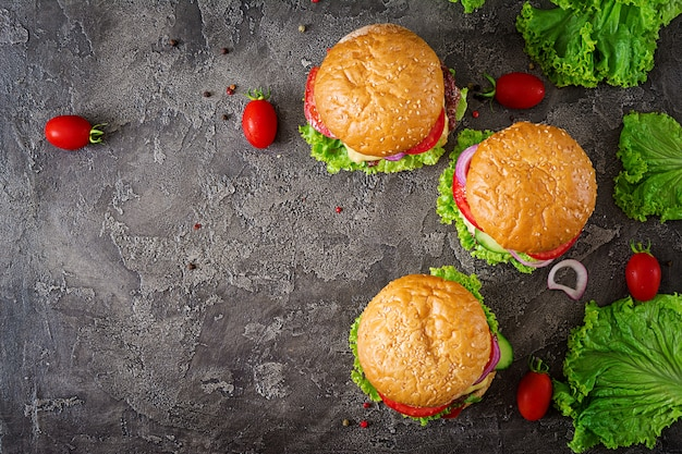 牛肉のハンバーガーと暗い背景に新鮮な野菜のハンバーガー。