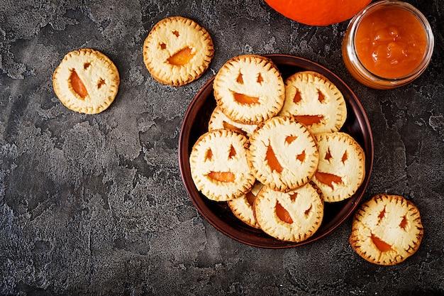 暗いテーブルの上のハロウィーンのジャックランタンカボチャのような形で自家製クッキー。