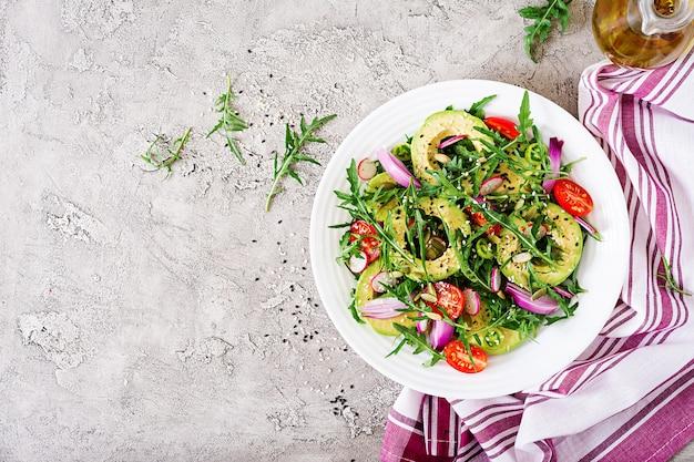 Полезный салат из свежих овощей - помидоров, авокадо, рукколы, редиса и семян на миске.