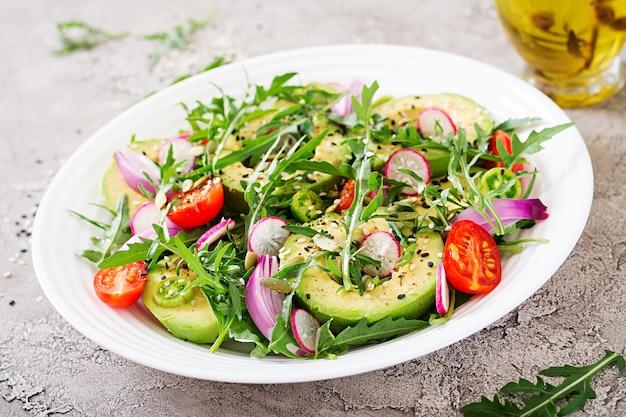 新鮮な野菜 - トマト、アボカド、ルッコラ、大根、ボウルに種のヘルシーサラダ。