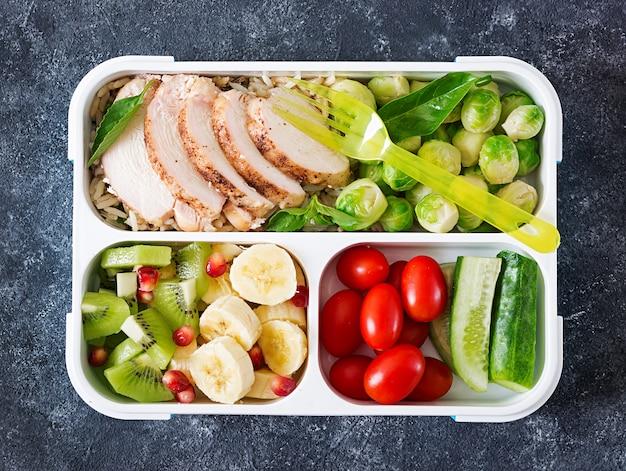 鶏ムネ肉、米、芽キャベツ、野菜、果物の入った健康的なグリーンミールの準備容器