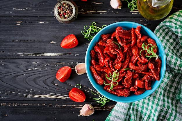 乾燥トマトとハーブと木製のテーブルの上にボウルにニンニク。イタリア料理。
