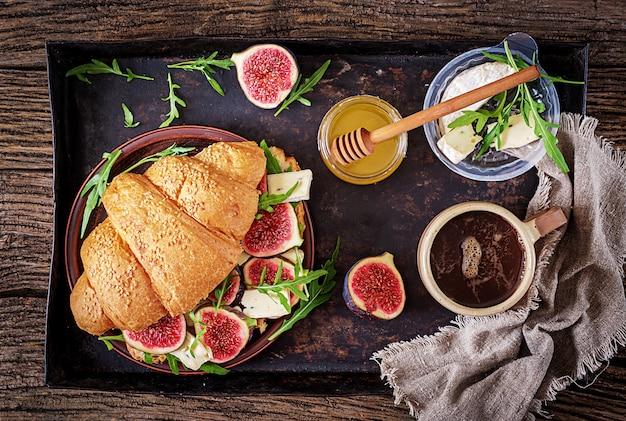 ブリーチーズルッコラとイチジクの焼きたてのクロワッサンサンドイッチ。美味しい朝食。