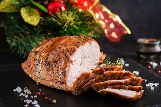 暗い素朴な背景に七面鳥のローストスライスクリスマスハム。祭りの食べ物。