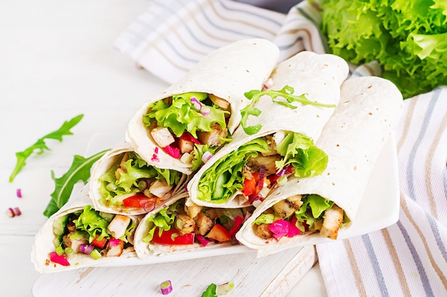 Мексиканская уличная еда фахита тортилла обертывает с куриным филе на гриле и свежими овощами.