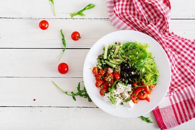 新鮮なキュウリ、トマト、ピーマン、レタス、タマネギ、フェタチーズ、ブラックオリーブのギリシャ風サラダ