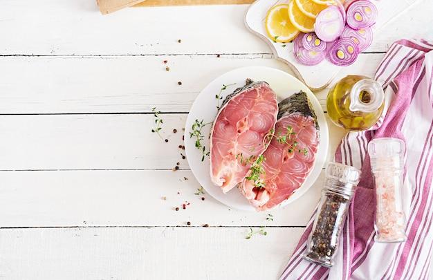 白い木製の背景にレモンとタイムの鯉魚の生ステーキ。