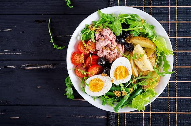 マグロ、インゲン、トマト、卵、ジャガイモ、ブラックオリーブのテーブルの上にボウルに健康的なボリュームのあるサラダ。