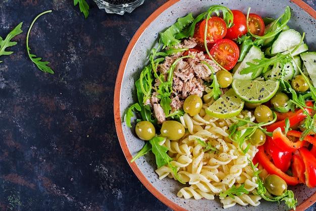 仏ボウル。マグロ、トマト、オリーブ、キュウリ、ピーマン、素朴な背景のルッコラのパスタサラダ
