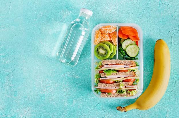 Коробка школьного обеда с бутербродом, овощами, водой и фруктами на столе.