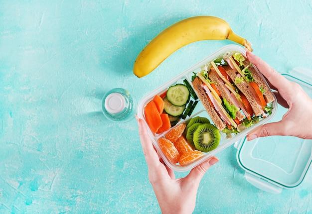 手でお弁当。サンドイッチ、野菜、水、テーブルの上の果物と学校のお弁当箱。健康的な食生活のコンセプトです。平らに置きます。上面図