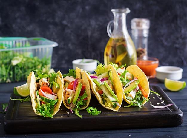 Мексиканские тако с куриным мясом, авокадо, помидорами, огурцами и красным луком.