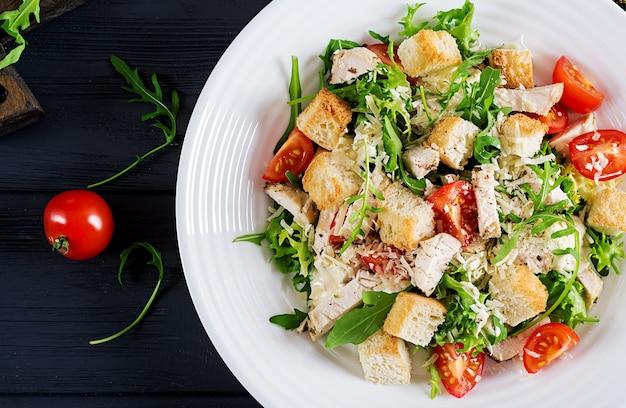 Полезный куриный салат цезарь на гриле с помидорами, сыром и гренками.