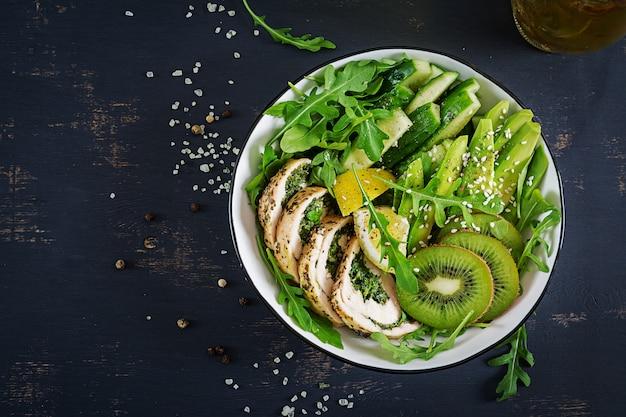 チキンの切り身、アボカド、きゅうり、新鮮なルッコラのサラダとゴマの丼もの。