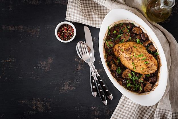テーブルの上のバルサミコソースのきのこ焼き鶏の胸肉。上面図