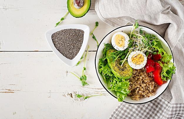 新鮮なサラダオートミール、パプリカ、アボカド、レタス、マイクログリーン、ゆで卵の朝食用ボウル。健康食品。菜食主義者の仏ボウル。上面図