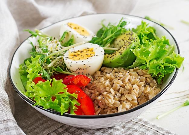 新鮮なサラダオートミール、パプリカ、アボカド、レタス、マイクログリーン、ゆで卵の朝食用ボウル。健康食品。菜食主義者の仏ボウル。