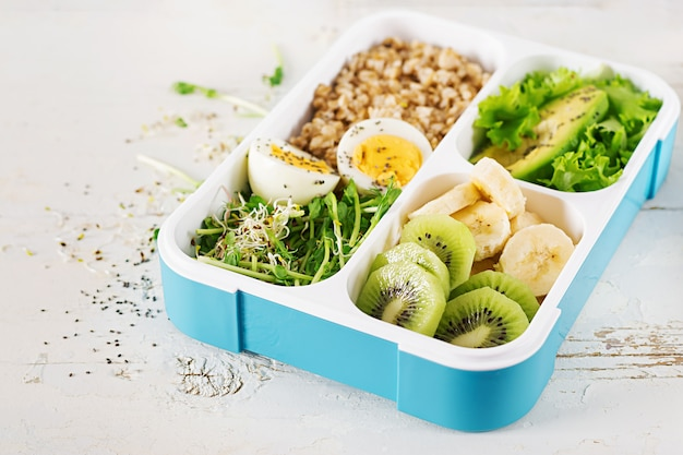 ゆで卵、オートミール、アボカド、マイクログリーン、フルーツのお弁当。健康フィットネス食品。取り除く。弁当箱。